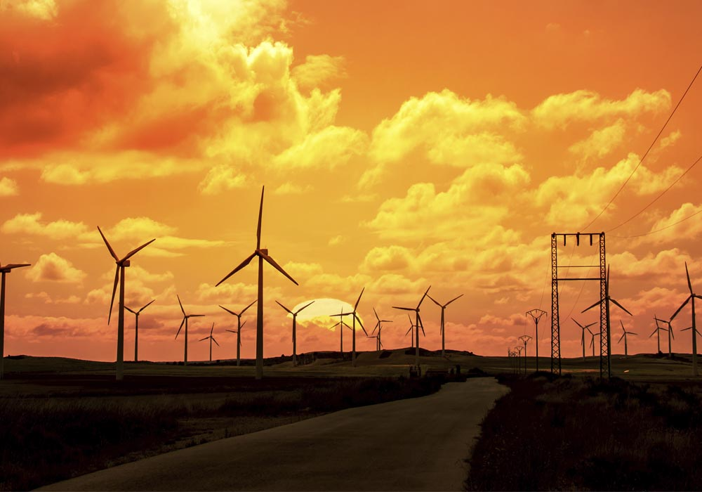 The sun sets behind wind power generators in Texas