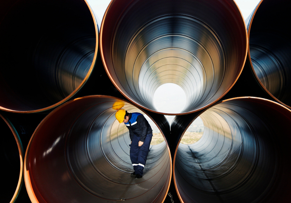Worker Inspecting Natural Gas Pipes